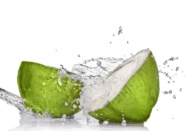 Green coconut with water splash isolated on white